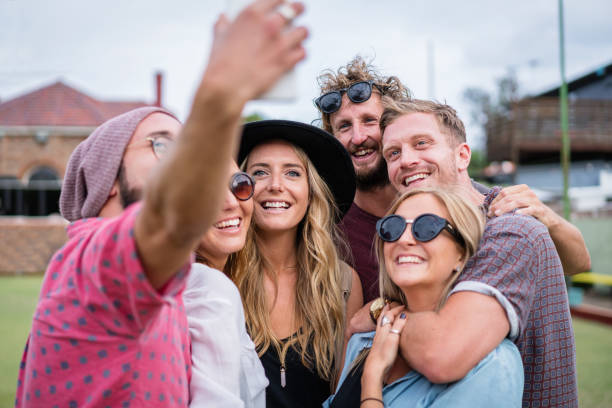 Smiling Group of Friends Shooting Selfies Having Fun stock photo