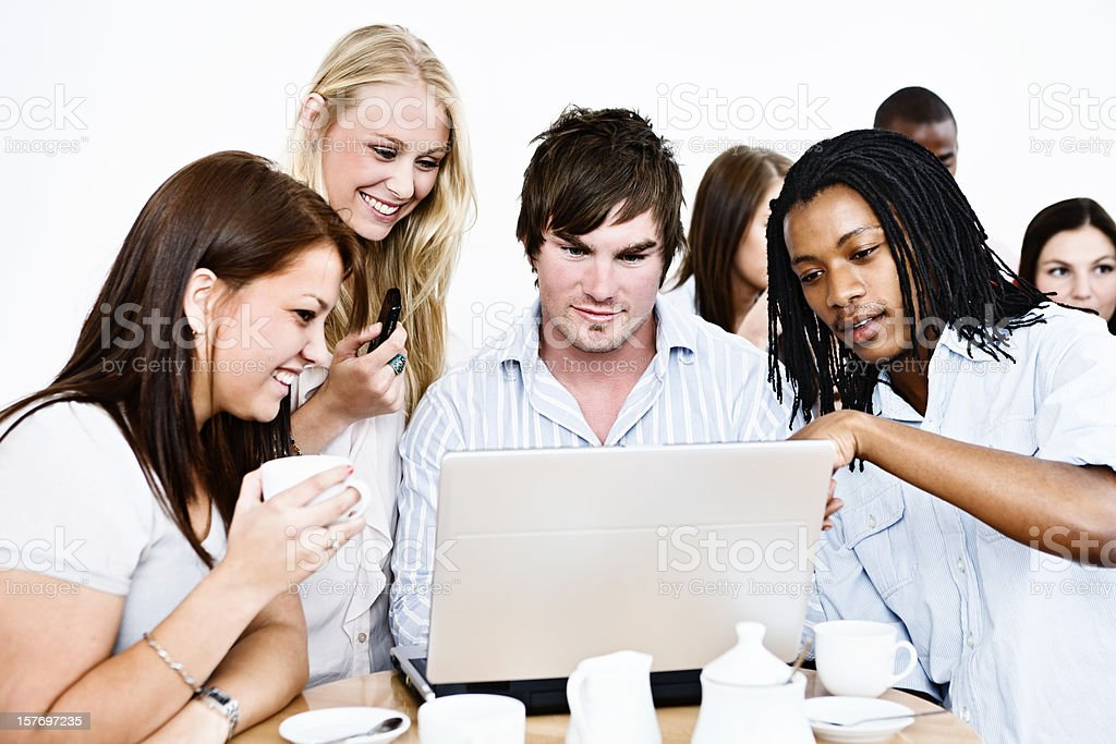 Smiling group of young people gathered round open laptop royalty-free stock photo