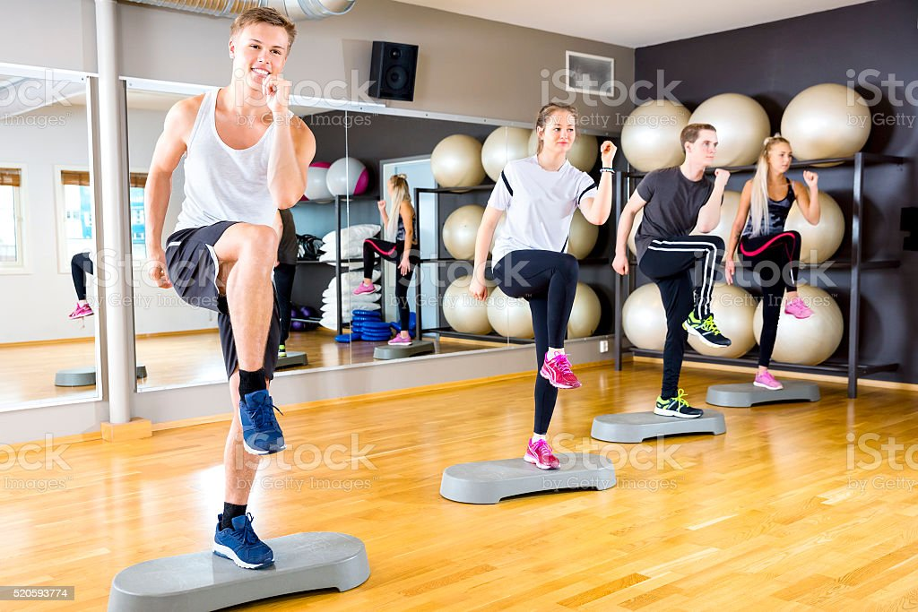 Smiling group raising legs on step platforms at fitness gym stock photo