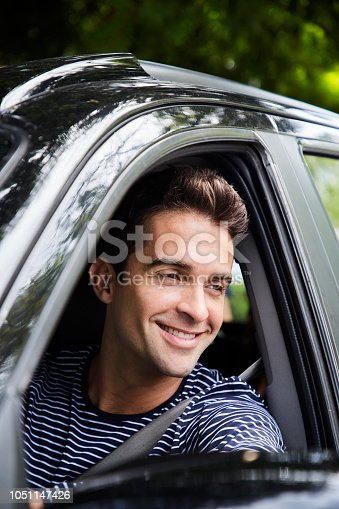 1051147634 istock photo Smiling guy in car 1051147426