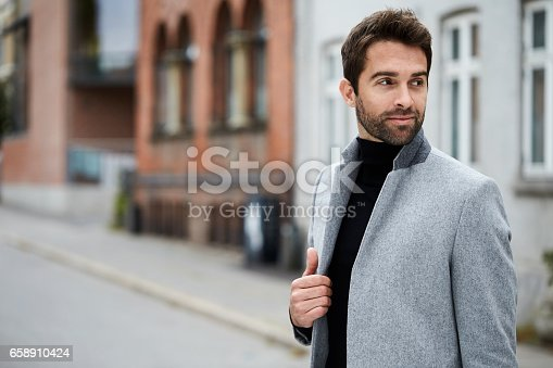Smiling guy in grey overcoat, looking away