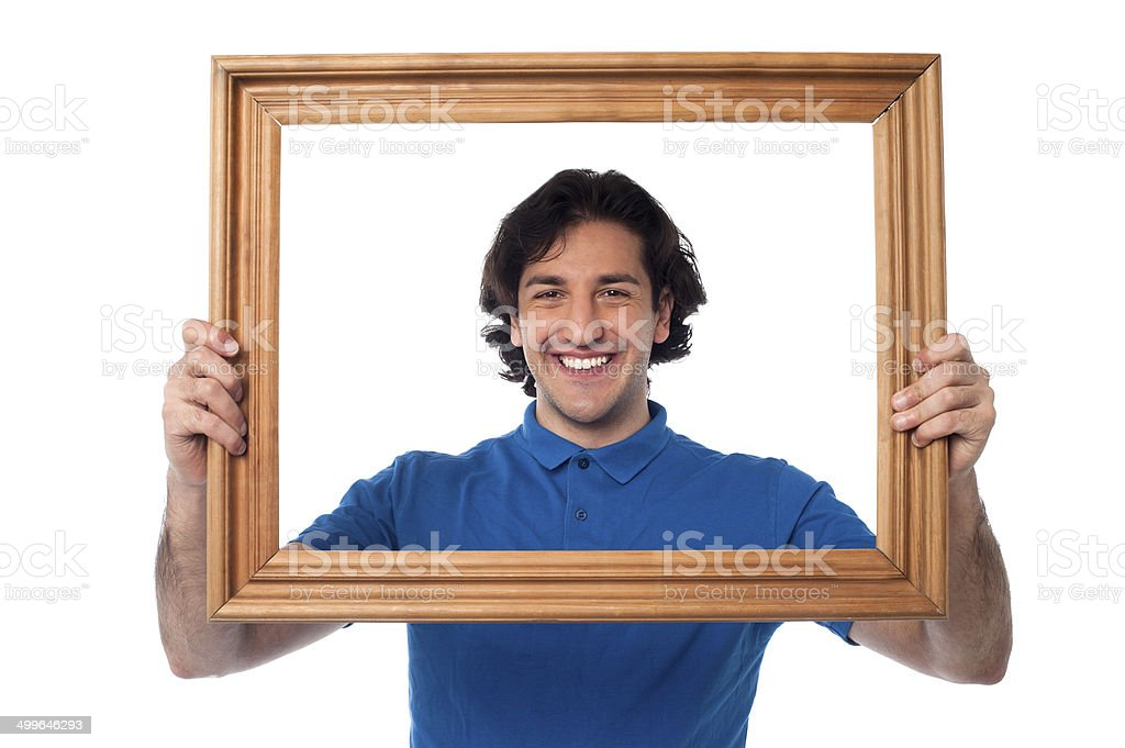 Smiling guy looking through picture frame royalty-free stock photo