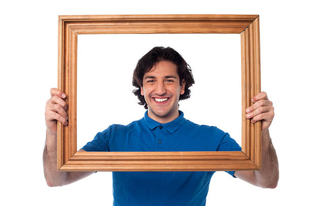 Smiling guy looking through picture frame stock photo