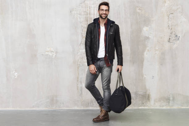 Smiling guy with bag Smiling guy with bag in studio, portrait leather jacket stock pictures, royalty-free photos & images
