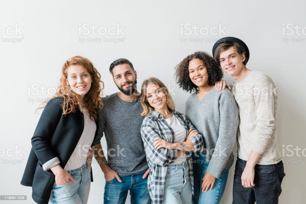 Lächelnde Jungs und Mädchen in Casualwear stehen an der weißen Wand vor der Kamera - Lizenzfrei Blick in die Kamera Stock-Foto