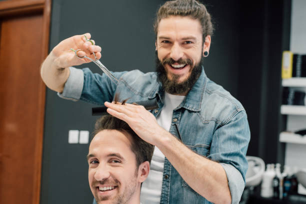 Smiling hairdresser with a man bun is giving a haircut Smiling handsome hairdresser with a man bun is giving a haircut to a happy young man man bun stock pictures, royalty-free photos & images