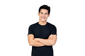 Smiling handsome Asian man in casual black t-shirt with arm crossed looking at camera studio shot isolated on white background