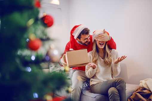 Smiling handsome bearded caucasian man covering his girlfriend's eyes and hiding gift behind back. Woman sitting on sofa. Both having santa hats on heads. Living room interior.