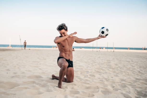 sorriso bonito homem brasileiro posando com estadio na praia - futebol de areia - fotografias e filmes do acervo