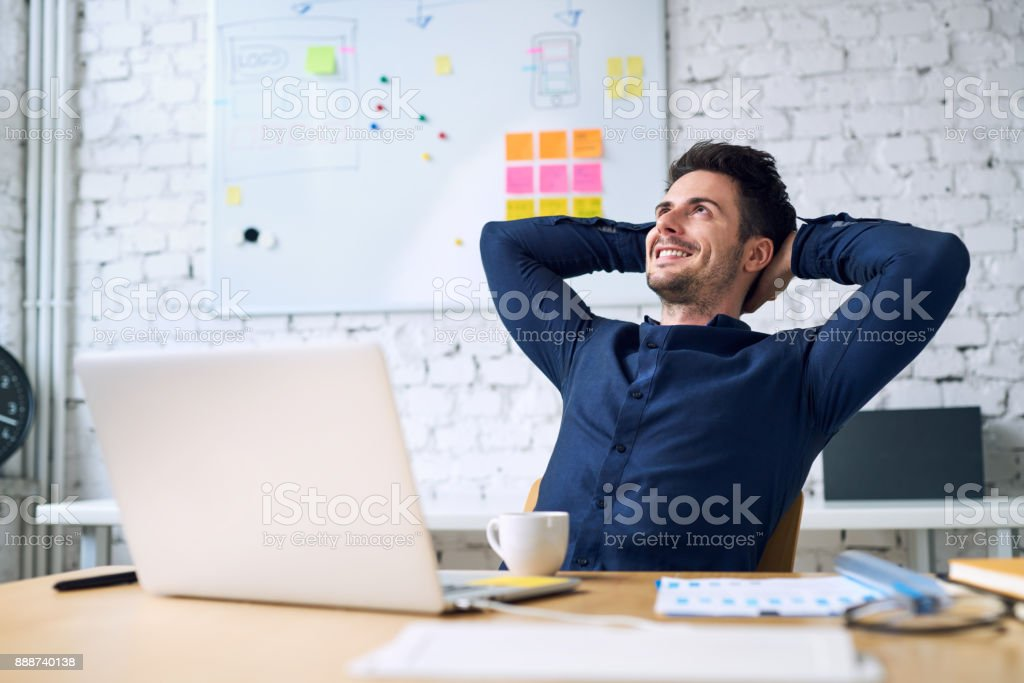 Smiling handsome businessman relaxing and enjoying coffee while taking break from work in office stock photo