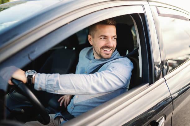 sonriendo el guapo hombre caucásico de conducir su coche y mirando por la ventana. de la mano en el volante. - conducir fotografías e imágenes de stock