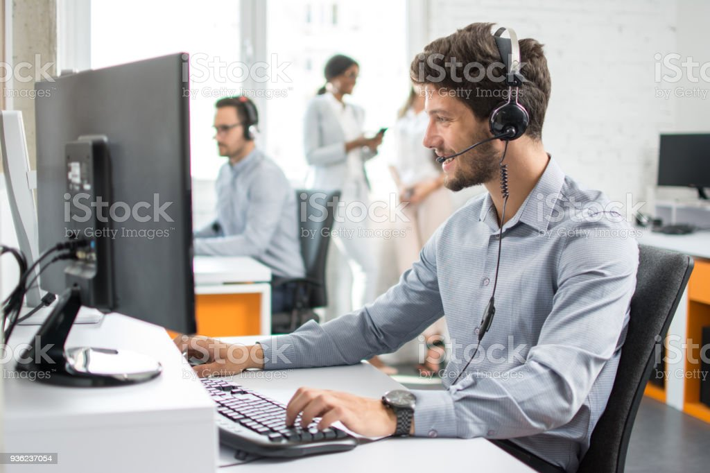 Smiling handsome customer support operator agent with hands-free device working in call center stock photo