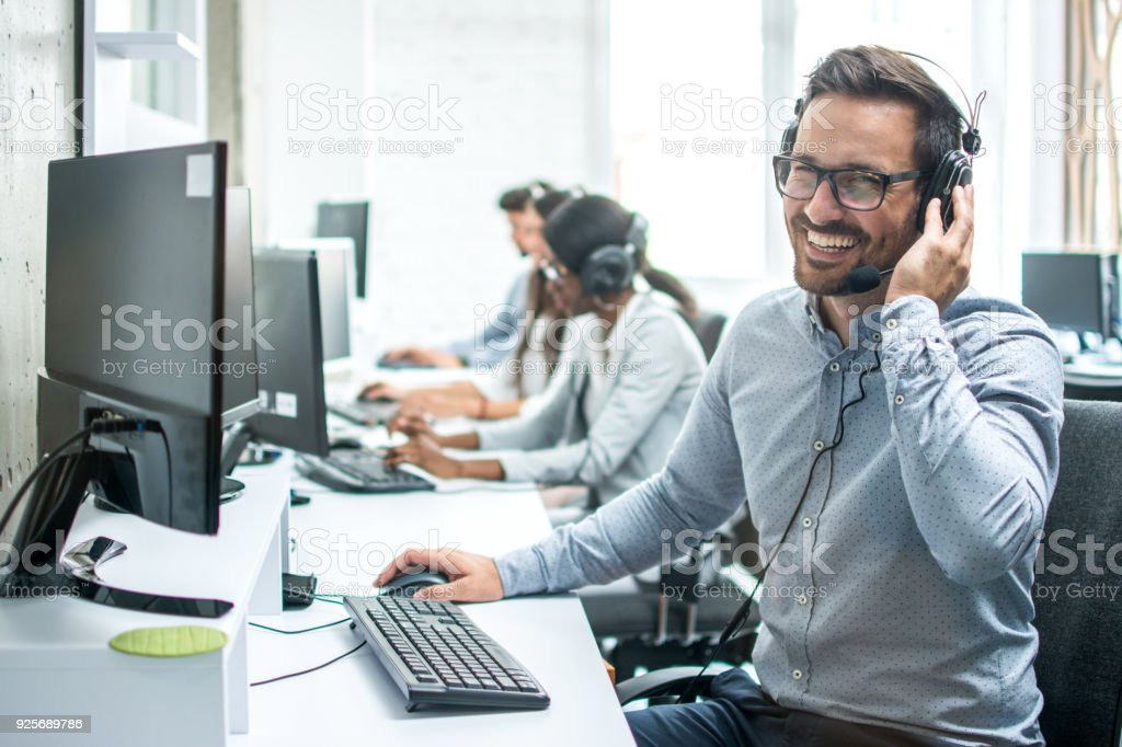 Smiling handsome customer support operator with headset working in call center. - foto stock