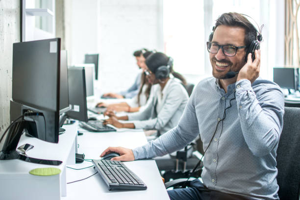Smiling handsome customer support operator with headset working in call center. stock photo