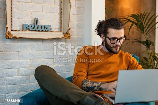 944652612 istock photo Smiling handsome freelancer working with laptop 1183838491