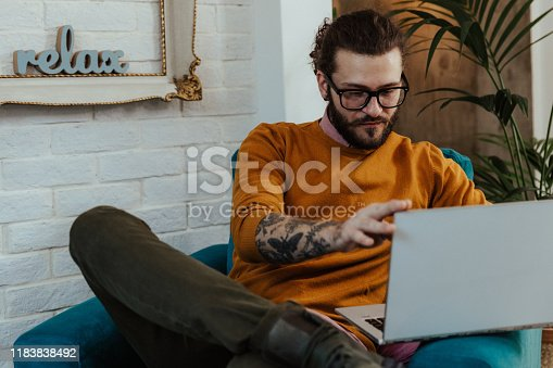 944652612 istock photo Smiling handsome freelancer working with laptop 1183838492