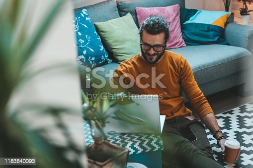 944652612 istock photo Smiling handsome freelancer working with laptop 1183840093