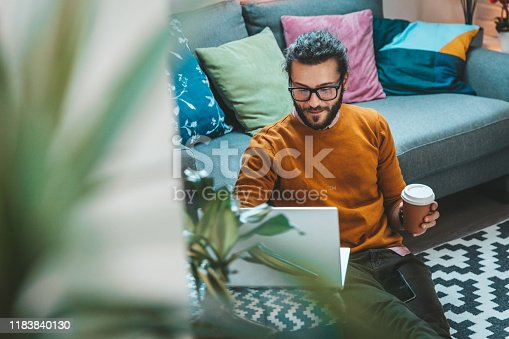 944652612 istock photo Smiling handsome freelancer working with laptop 1183840130