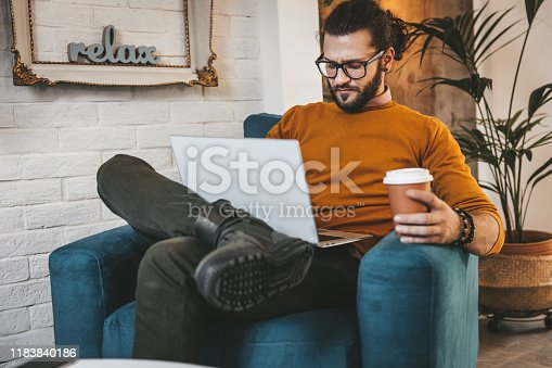 944652612 istock photo Smiling handsome freelancer working with laptop 1183840186