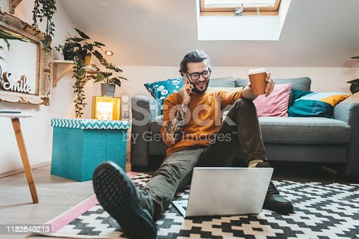 944652612 istock photo Smiling handsome freelancer working with laptop 1183840213