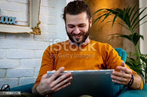 944652612 istock photo Smiling handsome freelancer working with laptop 1183841176