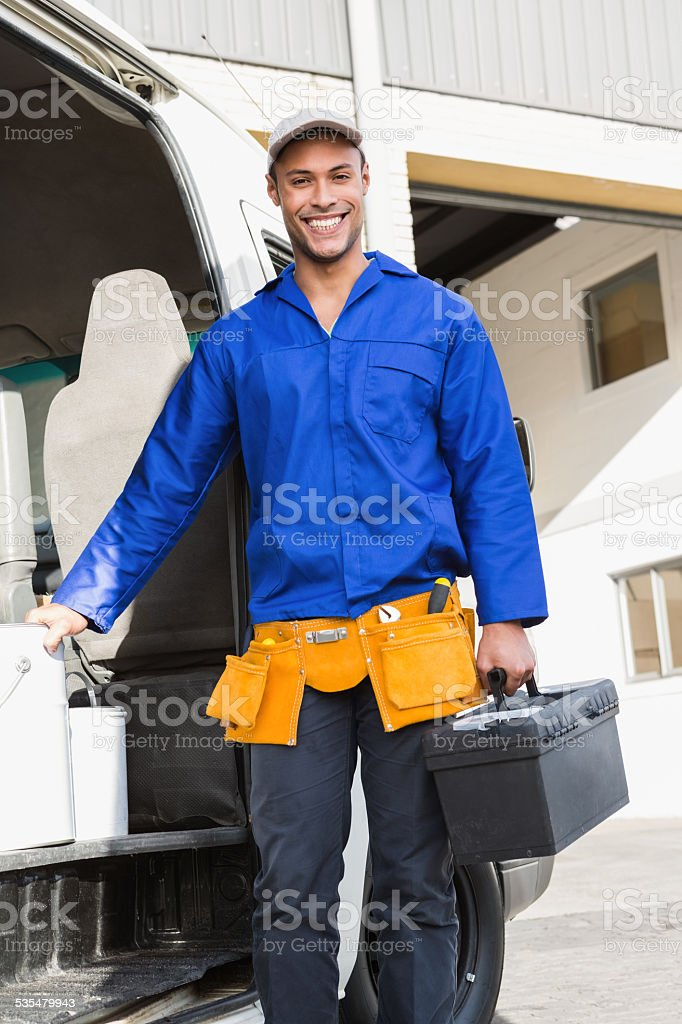 Smiling handsome handyman holding toolbox stock photo