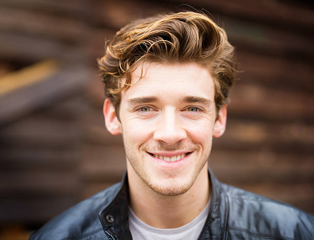 smiling handsome happy cheerful english male student wearing leather jacket - blond curly hair stockfoto's en -beelden