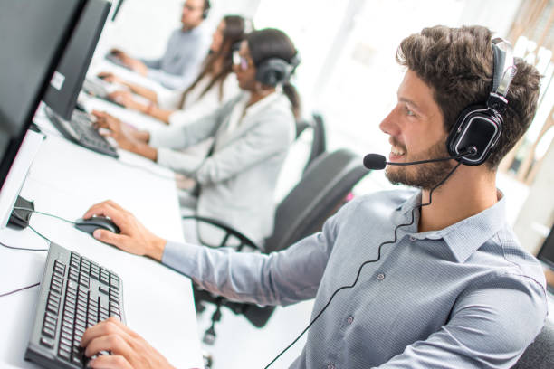 Smiling handsome male customer support phone operator with headset working in call centre. stock photo