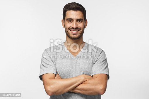 1045886560 istock photo Smiling handsome man in gray t-shirt standing with crossed arms isolated on grey background 1042466484