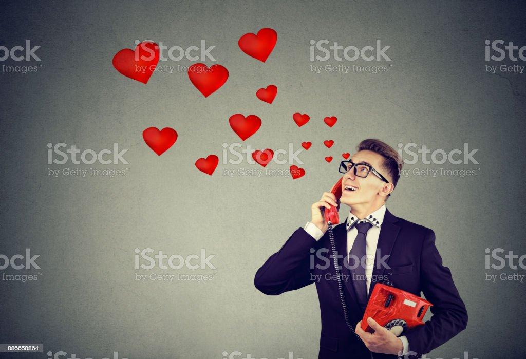 Souriant bel homme dans l'amour au téléphone - Photo