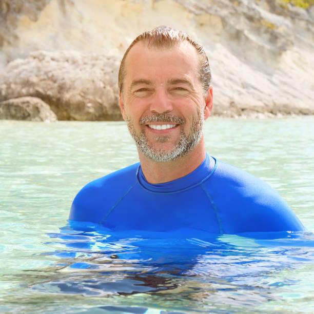 Lächeln auf den Lippen schöner Mann im Wasser – Foto