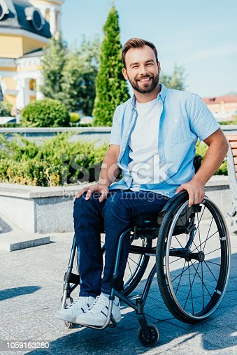 smiling handsome man in wheelchair looking at camera on street