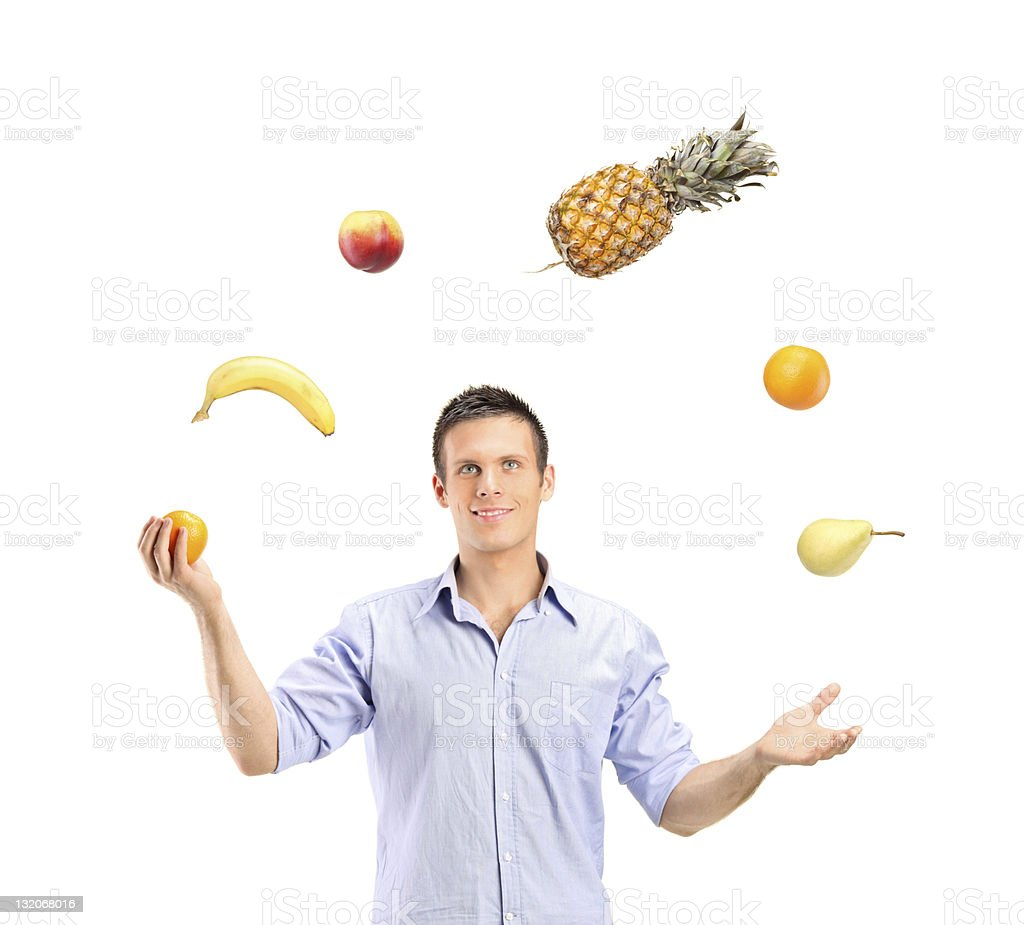 Smiling handsome man juggling fruits royalty-free stock photo