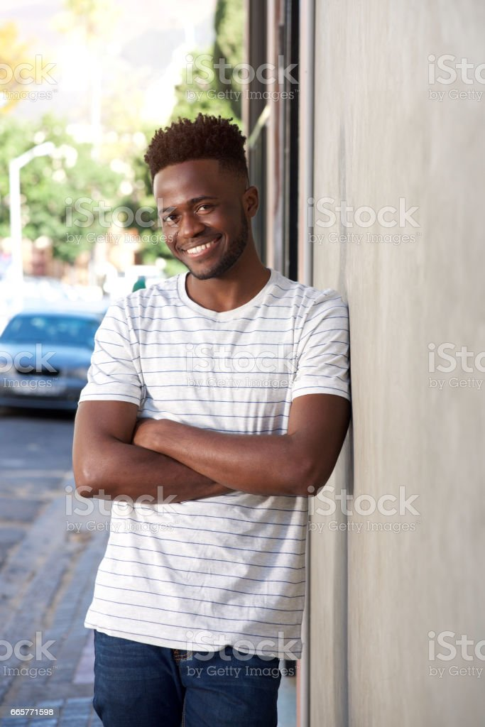 smiling handsome man leaning on wall outside on street stock photo