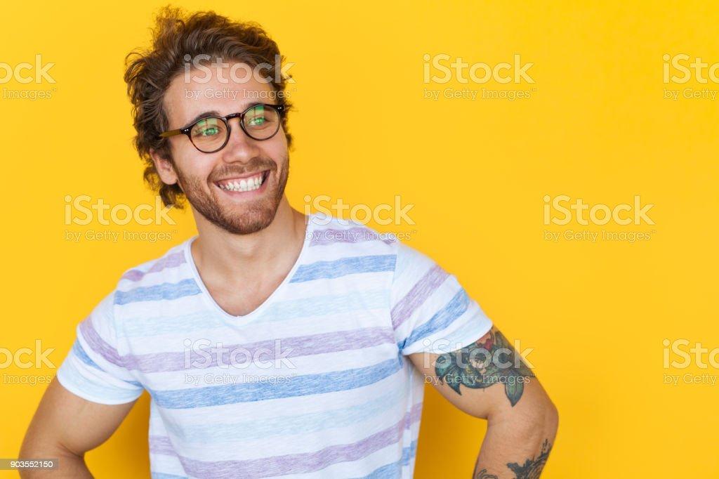 黄色のポーズ笑顔のハンサムな男 ロイヤリティフリーストックフォト