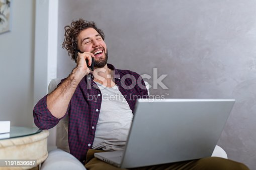 1127582480istockphoto Smiling handsome man talking on smartphone and using laptop computer while sitting at home. Young attractive smiling guy is browsing at his laptop and talking oh mobile phone, sitting at home 1191836687