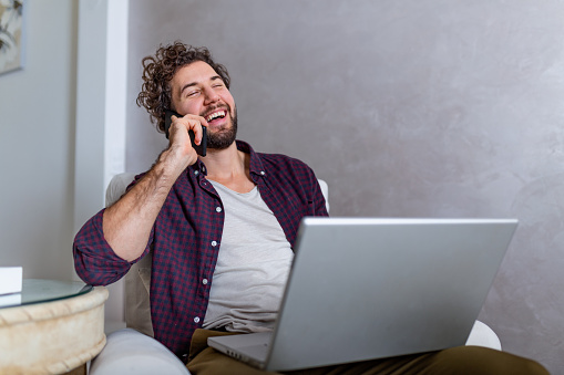 1127582480 istock photo Smiling handsome man talking on smartphone and using laptop computer while sitting at home. Young attractive smiling guy is browsing at his laptop and talking oh mobile phone, sitting at home 1191836687