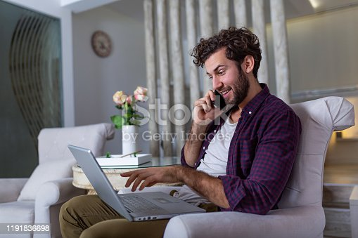 1127582480istockphoto Smiling handsome man talking on smartphone and using laptop computer while sitting at home. Freelance Career. Guy Talking On Cellphone Using Laptop Sitting On Floor At Home. Free Space For Text 1191836698