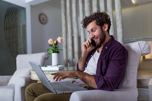 1127582480 istock photo Smiling handsome man talking on smartphone and using laptop computer while sitting at home. Freelance Career. Guy Talking On Cellphone Using Laptop Sitting On Floor At Home. Free Space For Text 1191836698