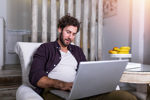 1127582480 istock photo Smiling handsome man talking on smartphone and using laptop computer while sitting at home. Young attractive smiling guy is browsing at his laptop and talking oh mobile phone, sitting at home 1213169856