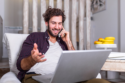 1127582480 istock photo Smiling handsome man talking on smartphone and using laptop computer while sitting at home. Freelance Career. Guy Talking On Cellphone Using Laptop Sitting On Floor At Home. Free Space For Text 1263539046