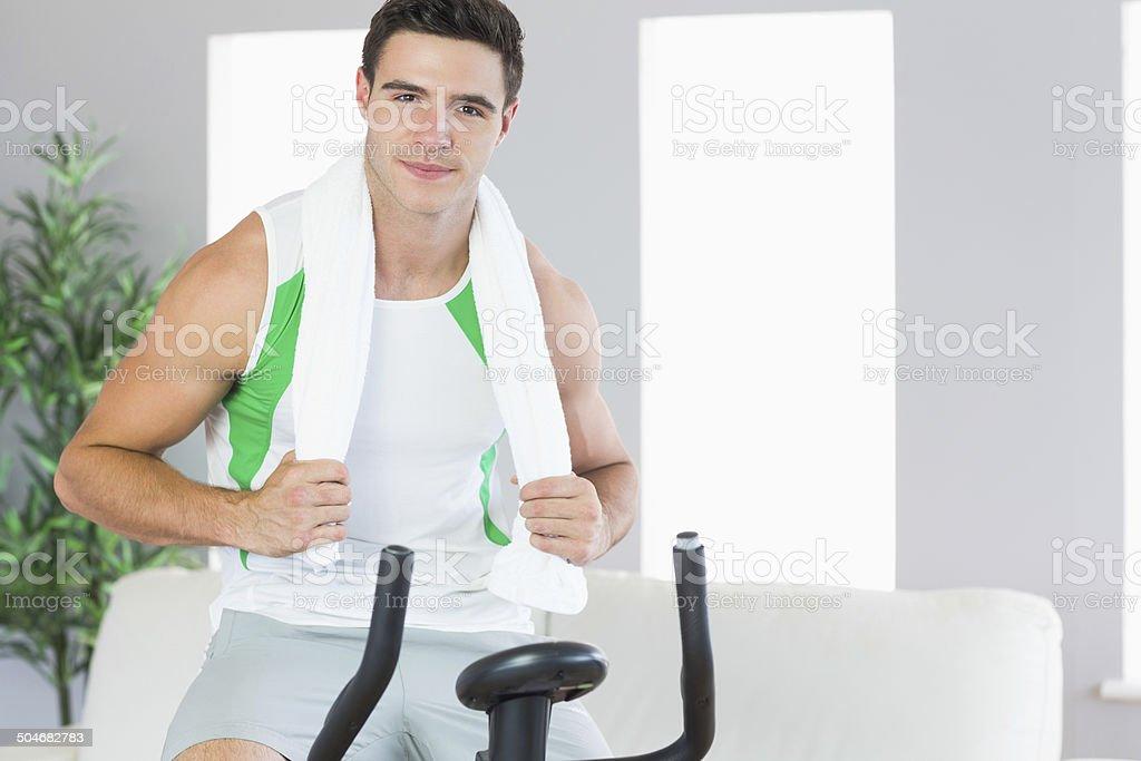 Sonriente hombre atractivo de entrenamiento en bicicleta fija - Foto de stock de Actividad libre de derechos