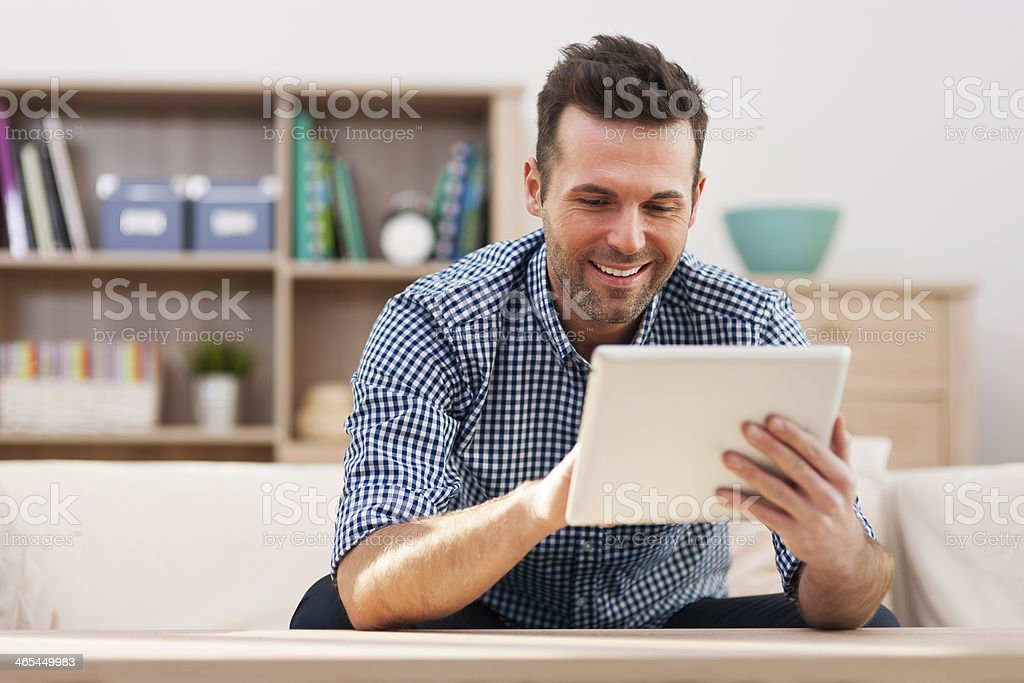 Smiling handsome man using digital tablet at home stock photo