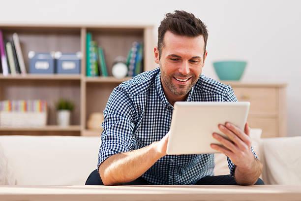 Lächelnd gut aussehender Mann mit digitalen tablet zu Hause – Foto