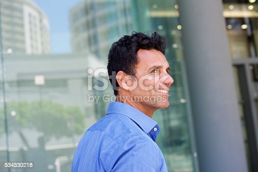 istock Smiling handsome man walking outside in the city 534330218
