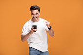 istock Smiling handsome man with mobile phone on yellow background. 1006571444