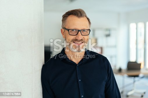 Indoor close-up portrait of a smiling handsome bearded middle-aged man in glasses and black shirt, leaning with his shoulder on white wall and looking at camera with friendly face, standing in office