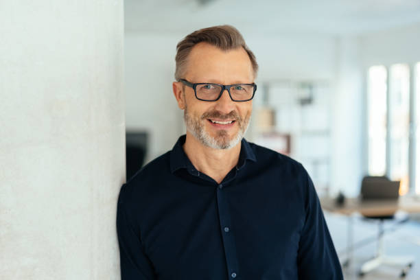Smiling handsome middle-aged man in black shirt stock photo