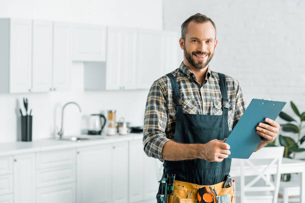 smiling handsome plumber holding clipboard and looking at camera in kitchen smiling handsome plumber holding clipboard and looking at camera in kitchen repairman stock pictures, royalty-free photos & images