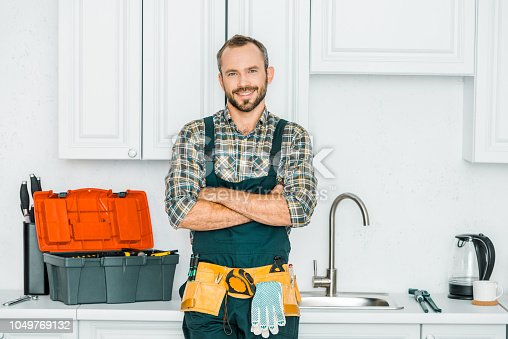 smiling handsome plumber standing with crossed arms and looking at camera in kitchen